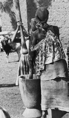 West African women grinding their diet staple, millet